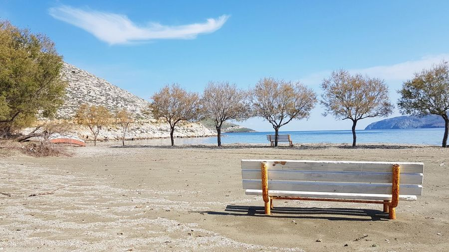 Bench on the beach Pebble Tree Roots  Calm Cloudscape Trees Boat Mediterranean Sea Greek Islands No People Outdoors Cloud Sea Beach Sand Water Absence Sky Bench Empty Park Bench Sun Lounger
