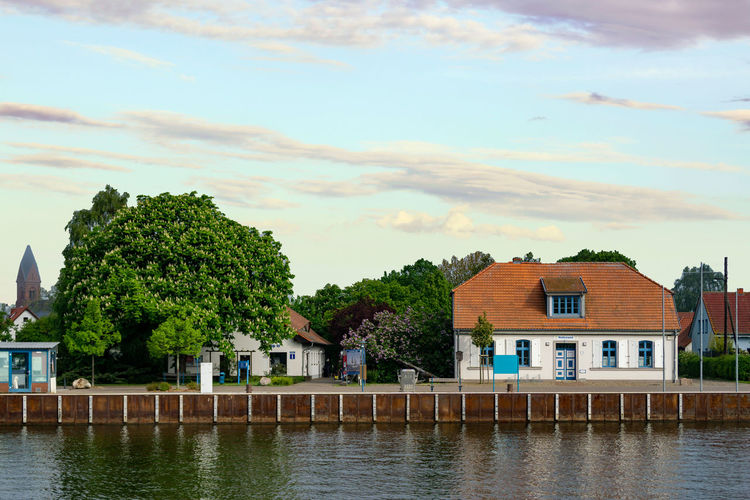 building in the harbor of the city of greifswald Built Structure Architecture Building Plant House Cloud - Sky Building Exterior Tree Water Waterfront River Sky Outdoors No People Residential District Nature Day City Growth