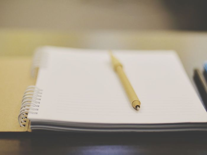 Close-up of pen and spiral notebook on table