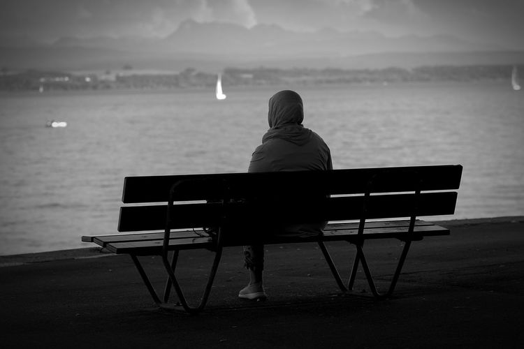 Rear view of man sitting on bench at sea shore