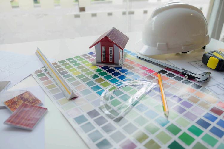 High angle view of color swatch with model home and hardhat on table