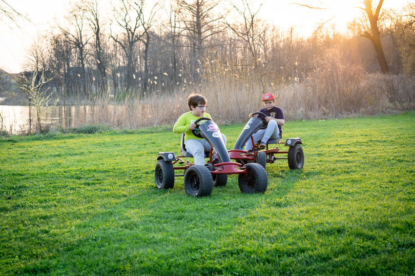 Kids having fun Cart Wheel Children Trees Boys Day Field Grass Lake Land Land Vehicle Leisure Activity Lifestyles Mode Of Transportation Nature Outdoors Park People Real People Riding Sports Sunset Togetherness Transportation Tree Two People #FREIHEITBERLIN