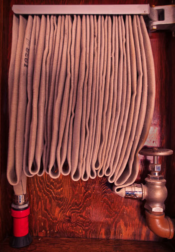 Vintage Commercial Structure Interior Hanging Fire Hose in Wood Cabinet Indoors  Close-up Wood - Material Still Life Industry Hanging Vintage Antique Fire Hose Industrial Interior Commercial Structure Real People Wood Cabinet Wall FireFighting  Fire Suppression