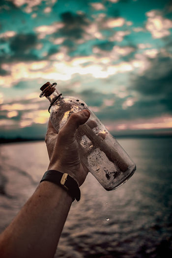 Message in a bottle Baltic Sea Dramatic Sky A Bokeh Bottle Close-up Focus On Foreground Glass Holding Human Body Part Human Finger Human Hand Men Message One Animal One Person Outdoors Real People Sculpture Sea Sky Statue Sunrise Sunset Water