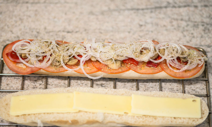 High Angle View Of Vegetable Slices And Cheese On Baguette At Table