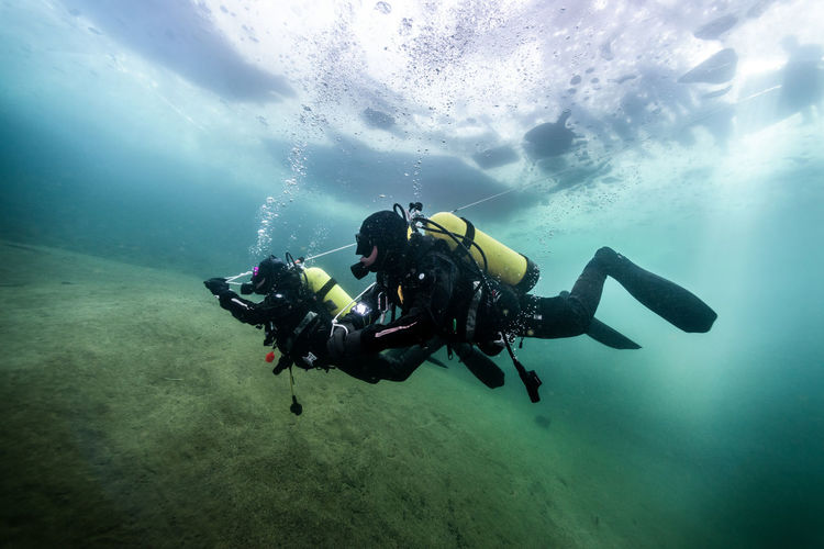 Side View Of Scuba Divers Under Water