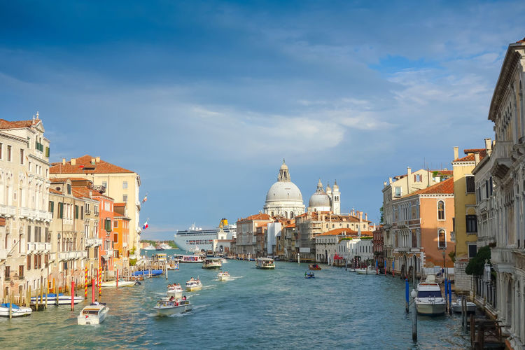 Boats sailing on grand canal by santa maria della salute against sky