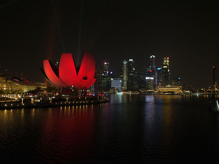 Illuminated artscience museum by river in city at night