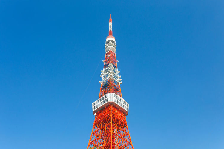 Low angle view of communication tower against blue sky