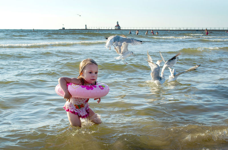 Cute Girl With Inflatable Ring By Seagulls In Lake