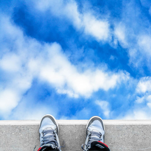 Low section of woman standing against blue sky