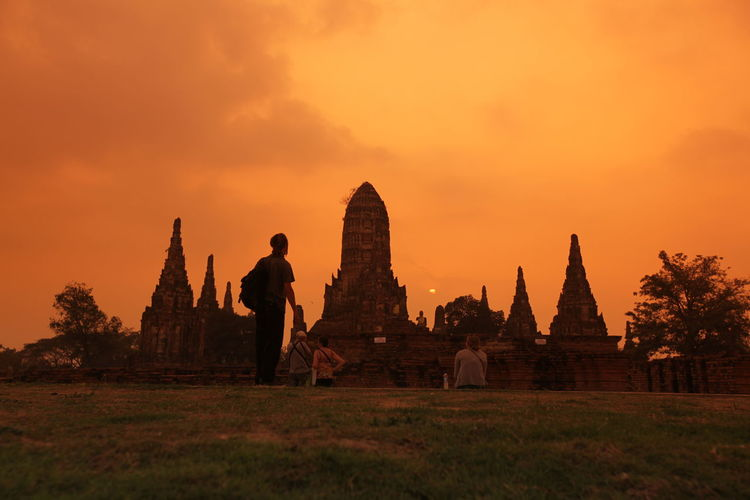 Tourists visiting historic temple in ayutthaya kingdom against sky during sunset