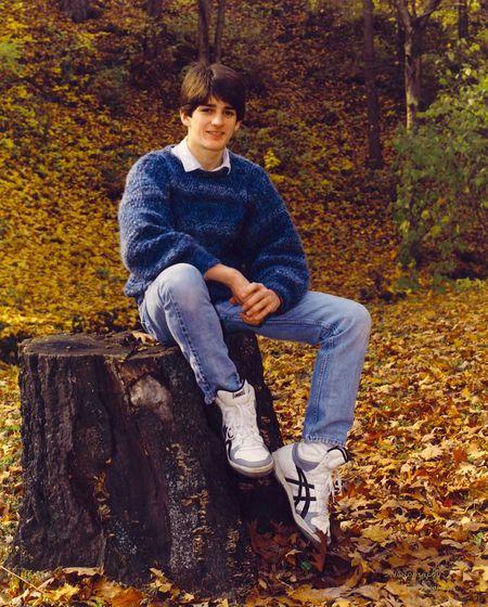 Full length portrait of teenage boy sitting on tree stump over field during autumn