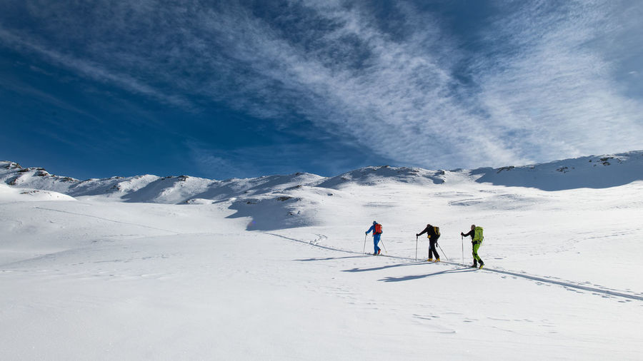 People skiing on snowcapped mountain against sky