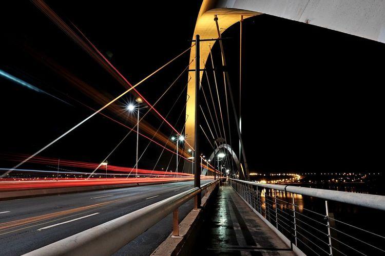 Light Trails On Suspension Bridge Against Sky At Night