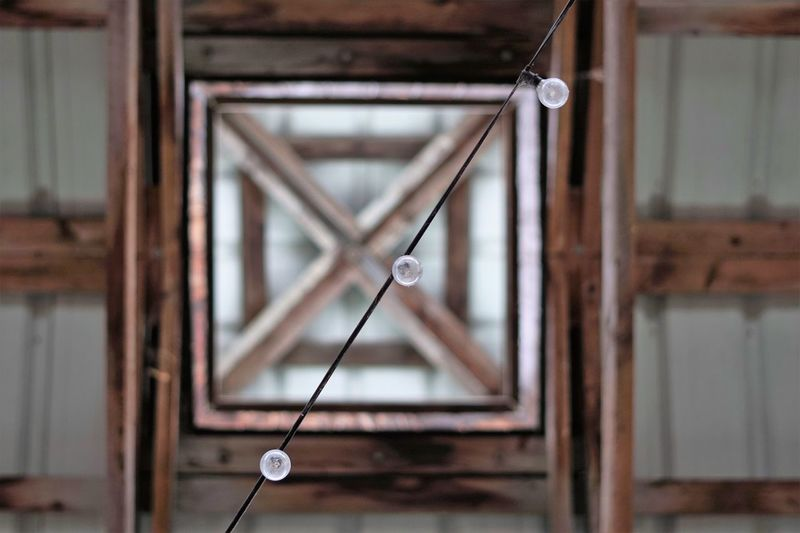 Close-up of electric lamp hanging on ceiling at home