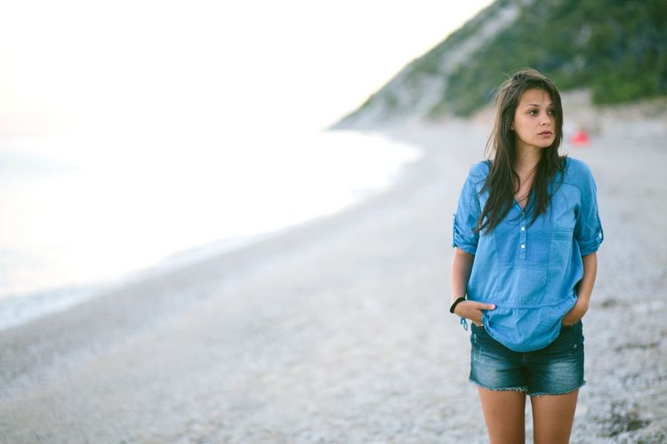 Young Woman Looking Away While Standing On Sand At Beach