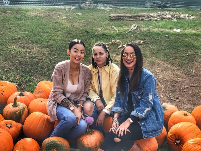 Pumpkin Smiling Sitting Happiness Friendship Portrait Jeans Togetherness Fun Day Casual Clothing Halloween Grass Cheerful Young Adult Looking At Camera Autumn Young Women Relaxation Leisure Activity