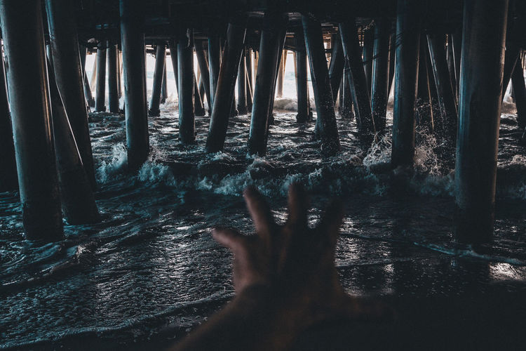 Cropped Image Of Woman Reaching Pier Over Sea