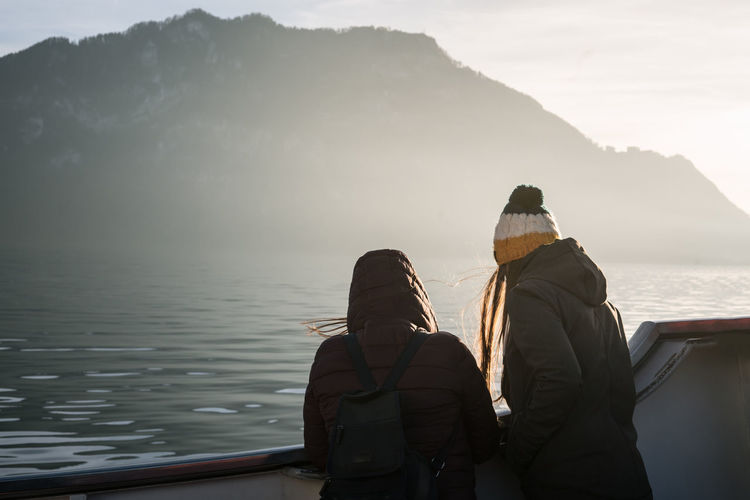 Female friends at lakeshore against mountains