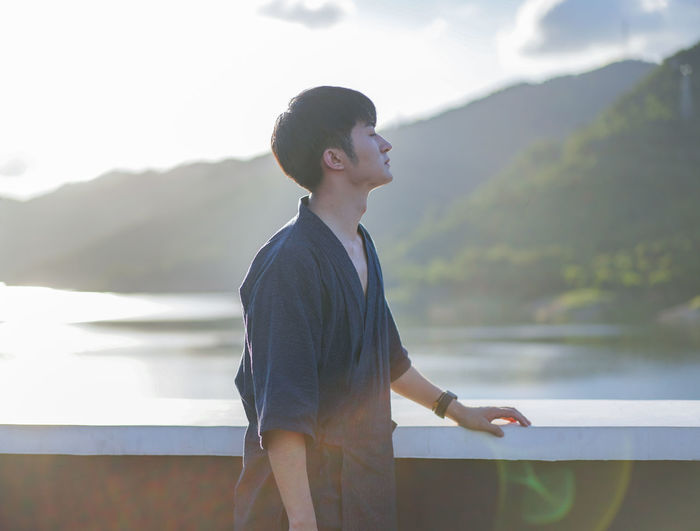 Side view of young man standing on lake