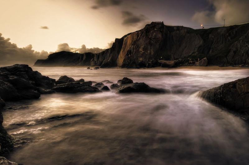 Scenic View Of Sea Against Rocky Coastline