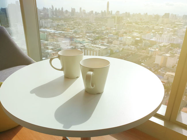 White cups on white table in sunlight. Two white coffee mugs in morning sunlight. Architecture Building Exterior Built Structure City Cityscape Coffee Coffee - Drink Coffee Cup Crockery Cup Day Drink Food And Drink Glass Mug Nature No People Outdoors Refreshment Relax Sunlight Table Tea Cup Transparent Window