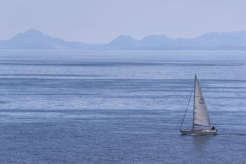 Into the big blue WeatherPro: Your Perfect Weather Shot Cloudscape Outer Hebrides Unrecognizable People Seascape Scotland Yacht Yachting Sport Water Nautical Vessel Sea Mode Of Transportation Transportation Mountain Beauty In Nature Sailboat Sailing Scenics - Nature Sky Tranquil Scene No People Tranquility Nature Day Travel Ship Idyllic Yacht Springtime Decadence