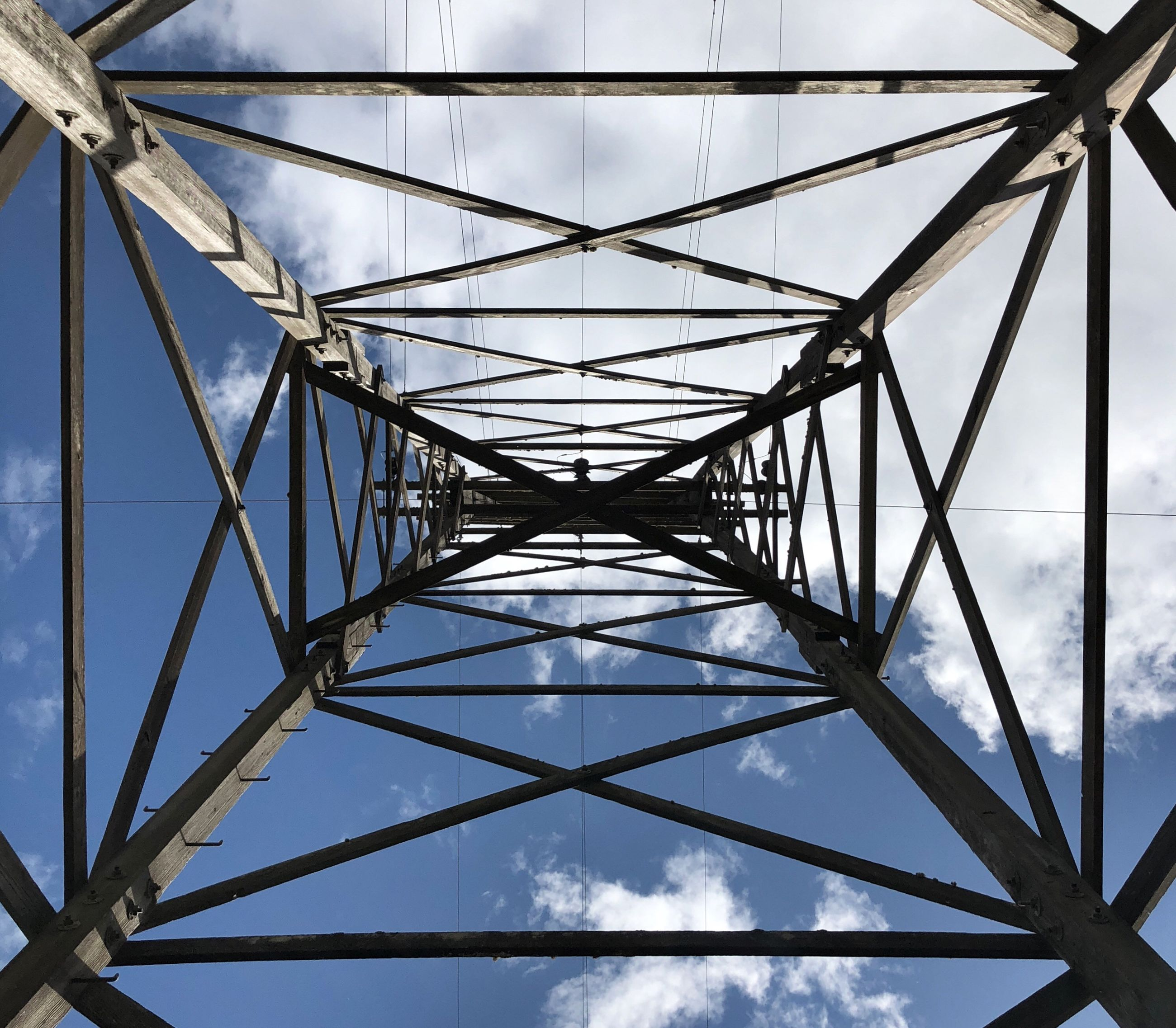 sky, metal, built structure, connection, electricity pylon, low angle view, no people, cable, architecture, nature, directly below, day, electricity, pattern, power line, power supply, fuel and power generation, technology, outdoors, sunlight, complexity, girder, steel, alloy