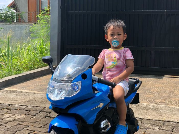 Portrait of cute boy with pacifier in mouth sitting on toy motorcycle on footpath