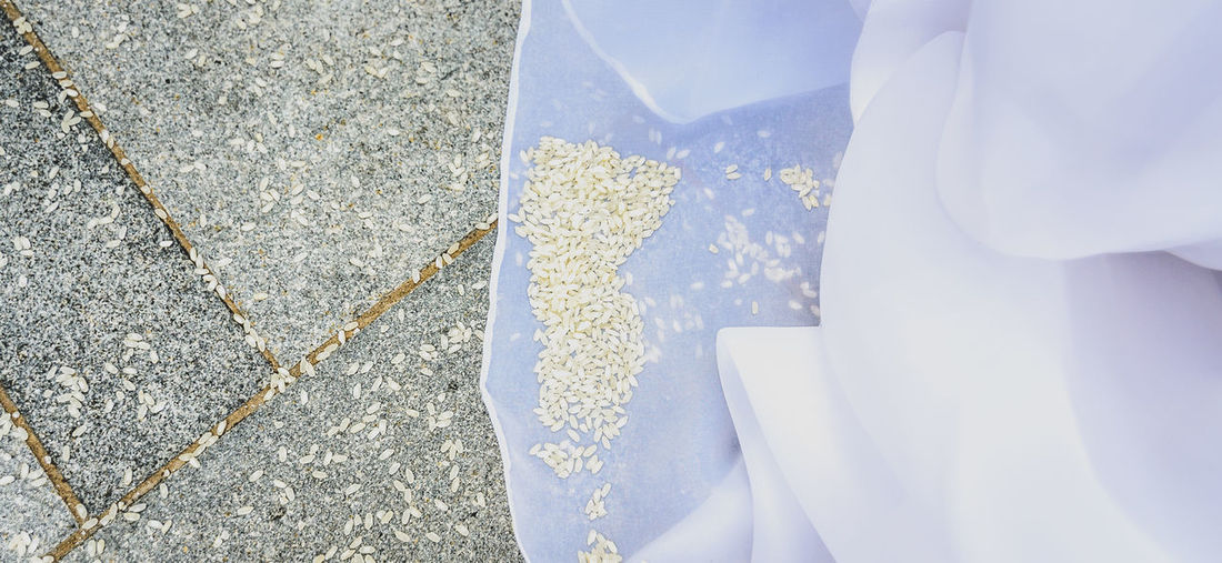 Detail of brides wedding dress with rice on the floor. Pavement full of rice after a wedding ceremony. Dress Flooring Rice Rice Paddy Tradition Wedding Bride Close-up Day Detail Floor High Angle View One Person Outdoors Pavement People Traditional Wedding Dress White