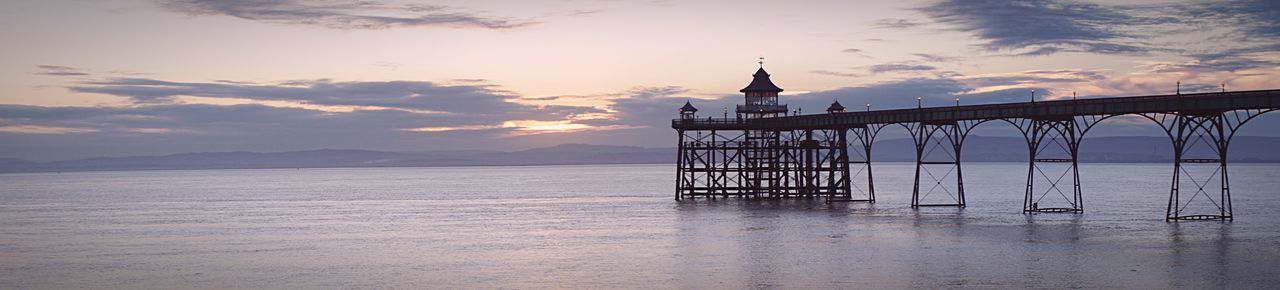 Panoramic view of pier over sea at sunset