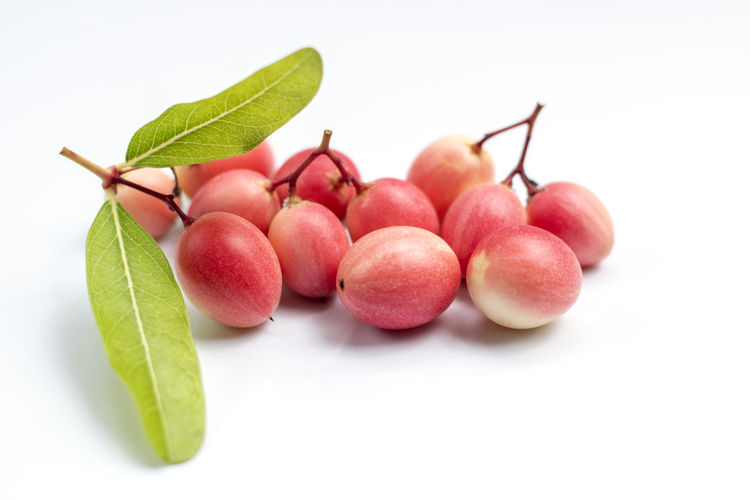 Close-up of fruits and leaves against white background