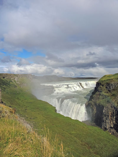 Beauty In Nature Cloud - Sky Scenics - Nature Environment Water Sky Grass Land Landscape Nature Tranquil Scene No People Day Plant Non-urban Scene Motion Sea Tranquility Idyllic Outdoors Flowing Water Gullfoss Waterfall Gullfoss Gullfoss Falls Gullfoss Iceland Iceland