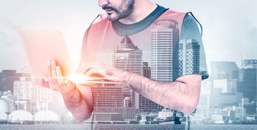 Digital composite image of man using mobile phone against buildings