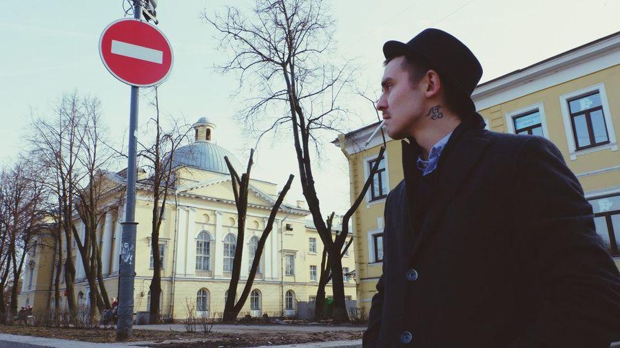 Man smoking cigarette street against buildings