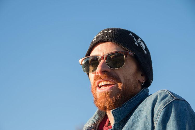 Portrait of man wearing sunglasses against clear blue sky