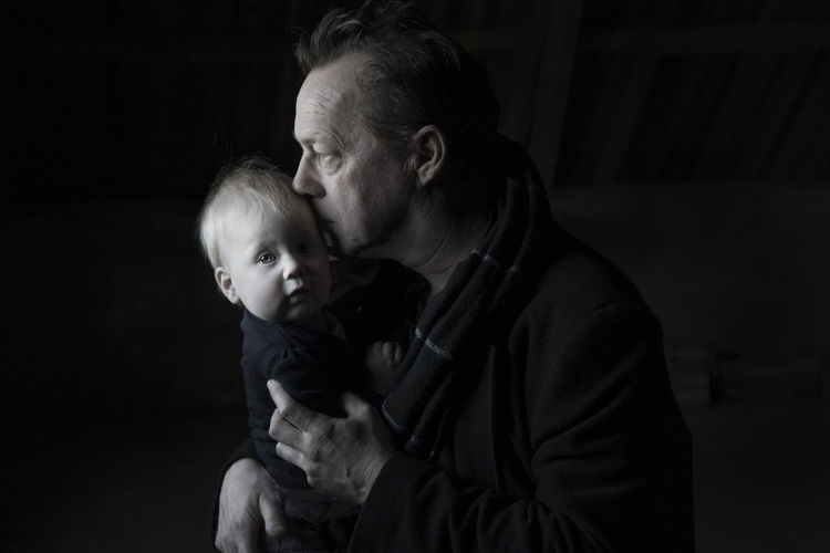 Close-up of grandfather carrying granddaughter against black background