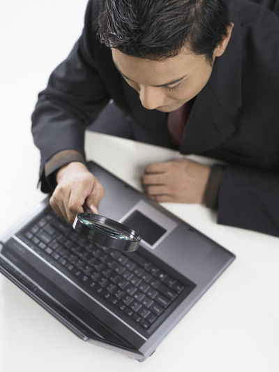 businessman holding a magnifying glass on keyboard Enlarge Looking At Camera Business Businessman Communication Computer Computer Keyboard Curious Day Doublt Indoors  Keyboard Laptop Looking For Answers Magnified Magnifying Glass Men One Person Real People Search Sitting Table Technology Using Laptop Wireless Technology