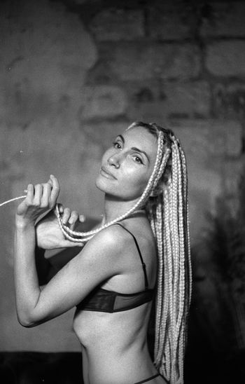 Side view of young woman with dreadlocks wearing bikini against wall