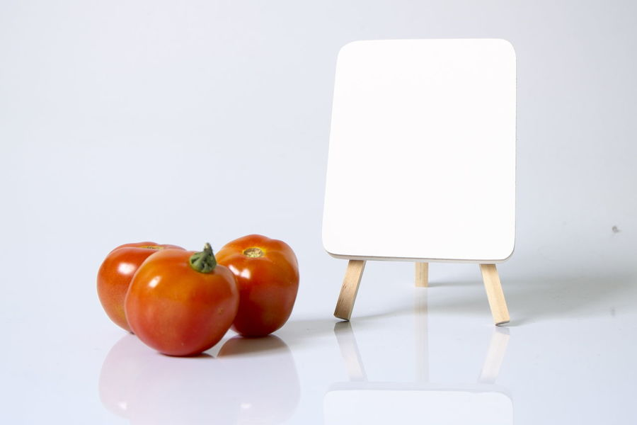 Tomatoes and blank white board on white background Blank Close-up Cooking Copy Space Day Food Food And Drink Freshness Healthy Eating Indoors  No People Orange Vegetables Tomato Vegetable White Board