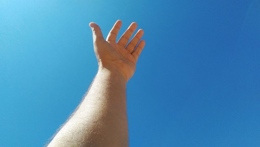 Cropped hand of man against clear blue sky during sunny day