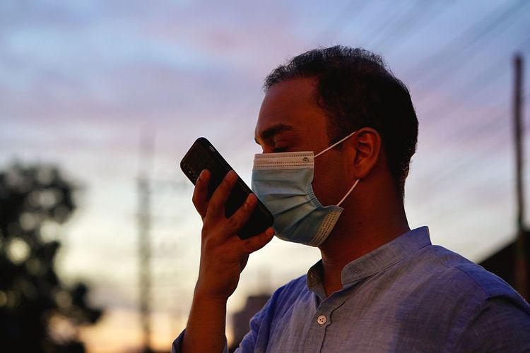 Man wearing ask talking on phone during sunset