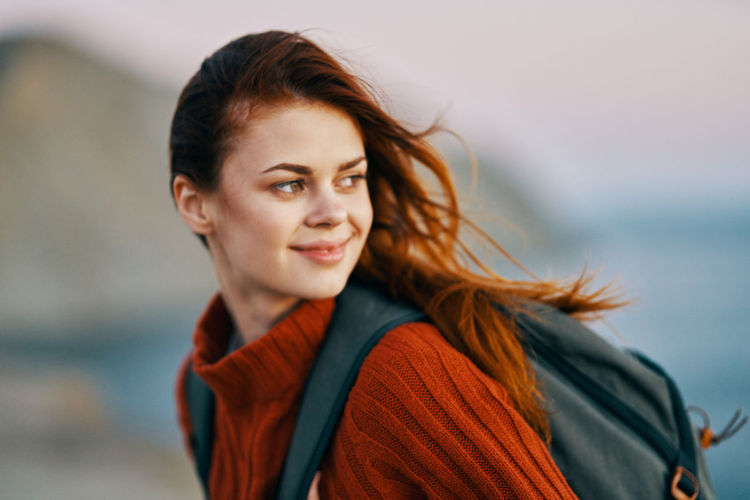 Portrait of smiling young woman looking away outdoors