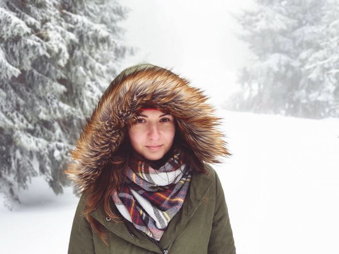 Portrait of young woman wearing warm clothing while standing in forest during winter