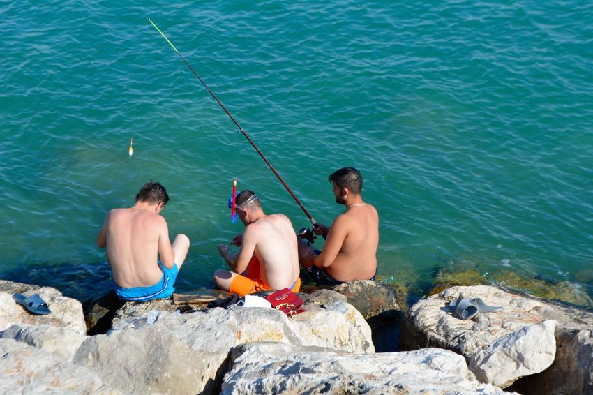 Fishing Hook Snorkeling Swimming Day Enjoyment Fishing Holiday Leisure Activity Lifestyles Males  Men Nature Outdoors People Rock Rock - Object Sea Shirtless Shorts Sitting Solid Trip Two People Vacations Water The Traveler - 2018 EyeEm Awards