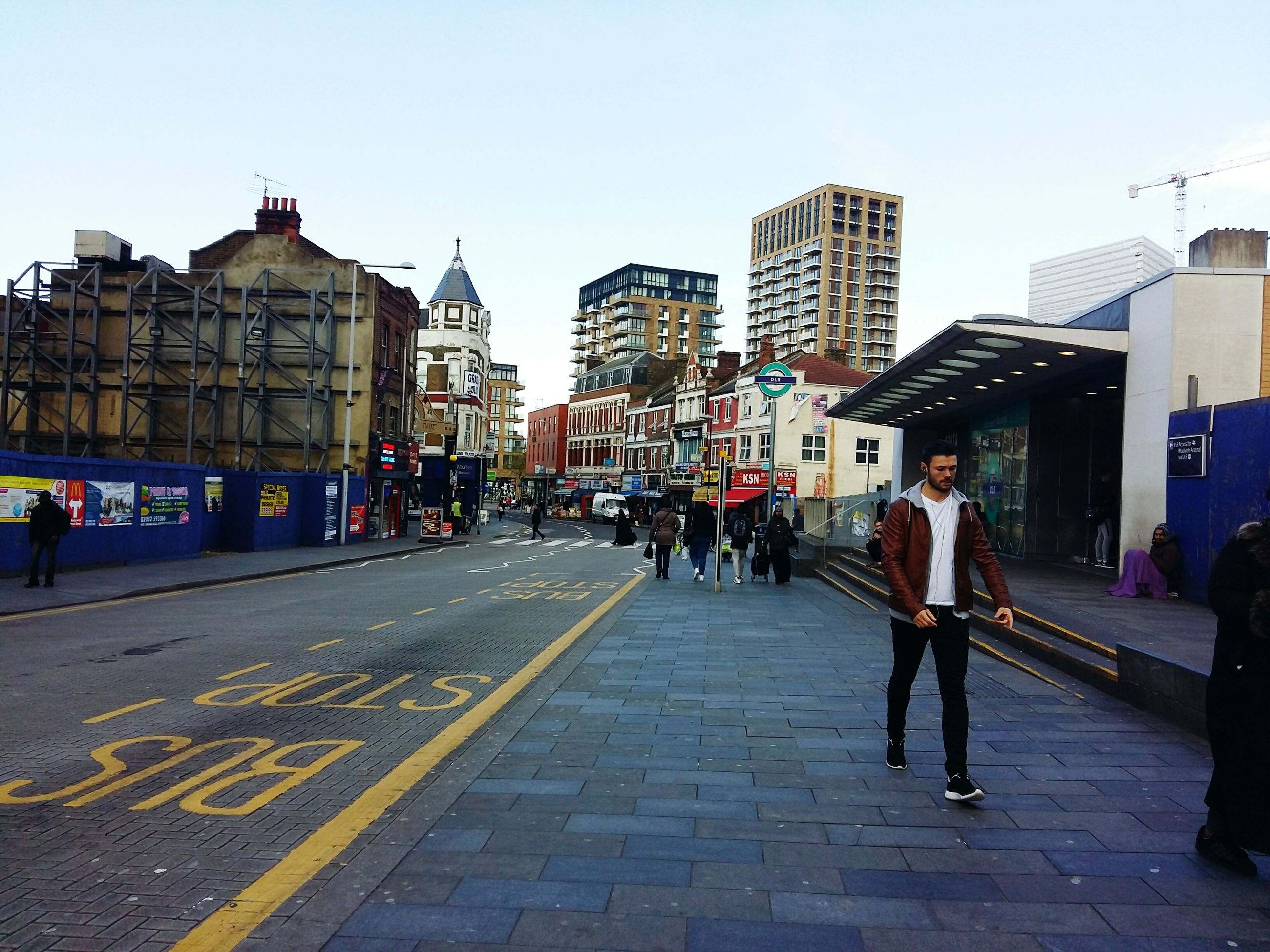 building exterior, architecture, built structure, men, city, clear sky, street, walking, person, large group of people, lifestyles, city life, transportation, road, the way forward, leisure activity, city street, sky, road marking