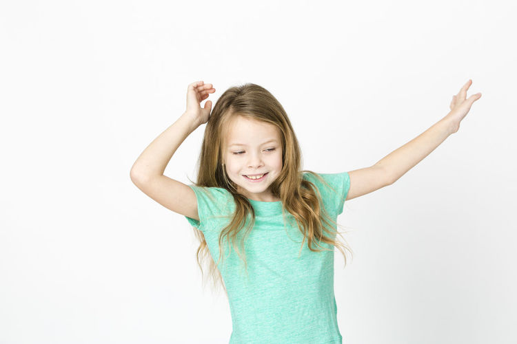 Cute Smiling Girl Dancing Against White Background
