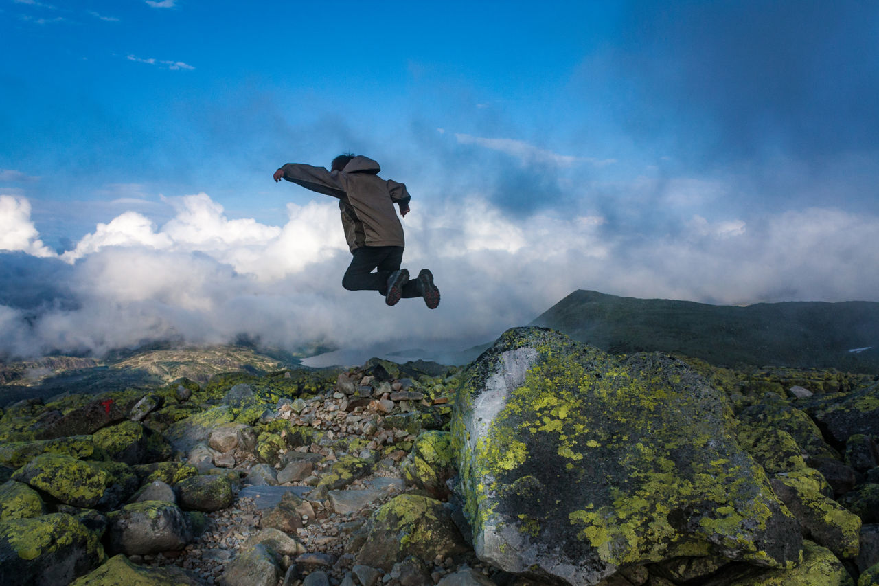 Rear view of a man jumping on landscape