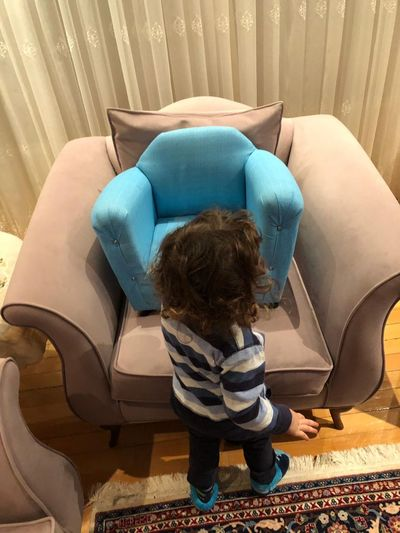 Annenin oğlu. One Person Real People Childhood Lifestyles Child Full Length International Women's Day 2019 Indoors  Leisure Activity Curly Hair High Angle View Furniture Rear View Women Casual Clothing Sitting Toddler  Females Home Interior Day Hairstyle